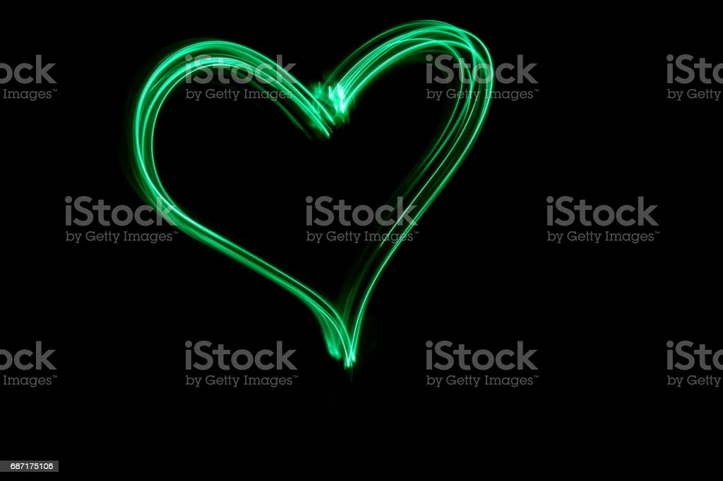 Green Light Painting Photography - heart symbol against a black background stock photo