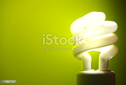 an energy saving light bulb on a green background.