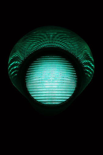 Green single traffic light in the night. Other traffic lights in: