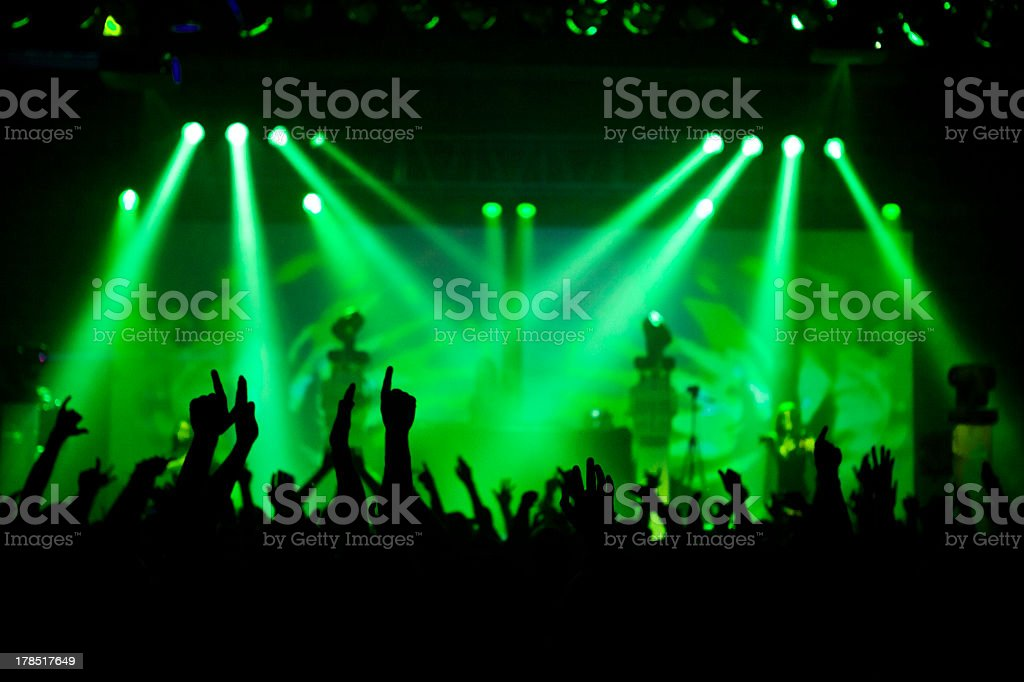 Green lights illuminate a concert stage and its crowd  stock photo