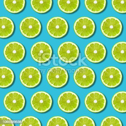 Green lime slices pattern on vibrant turquoise color background. Minimal flat lay food texture
