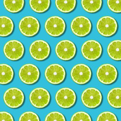 istock Green lime slices pattern on vibrant turquoise background 1065599538