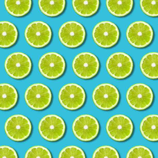 green lime slices pattern on vibrant turquoise background - pop art stock photos and pictures