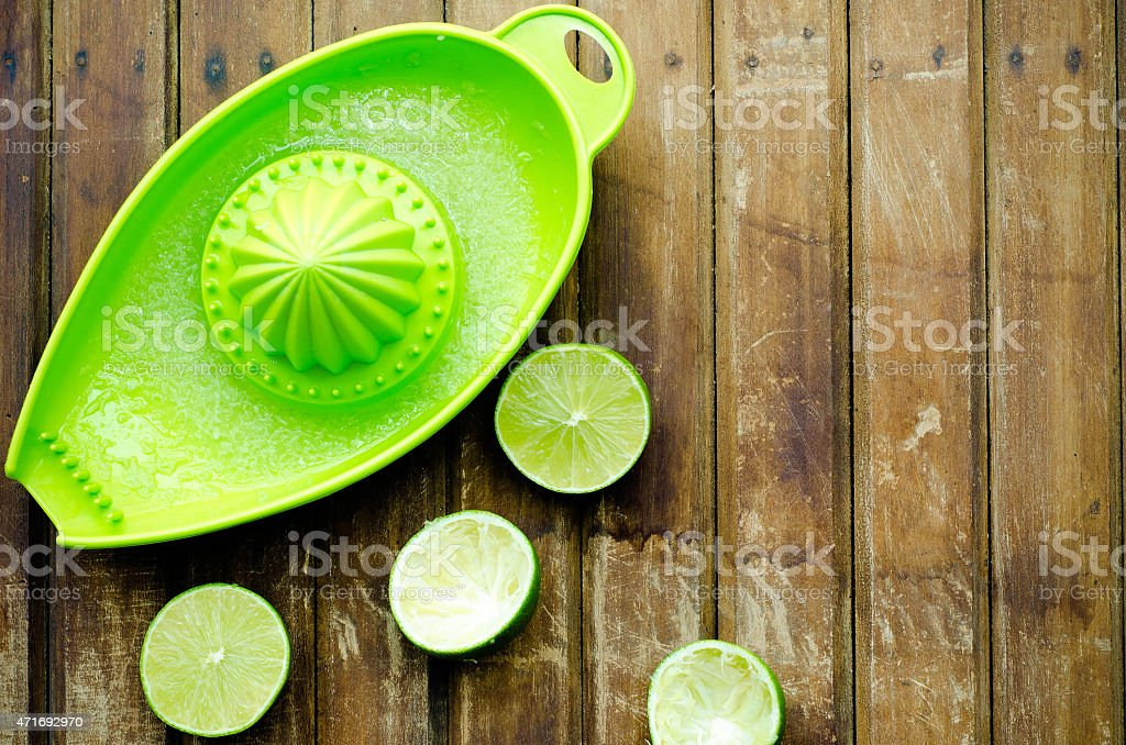 green limes with green manual juicer on the table stock photo