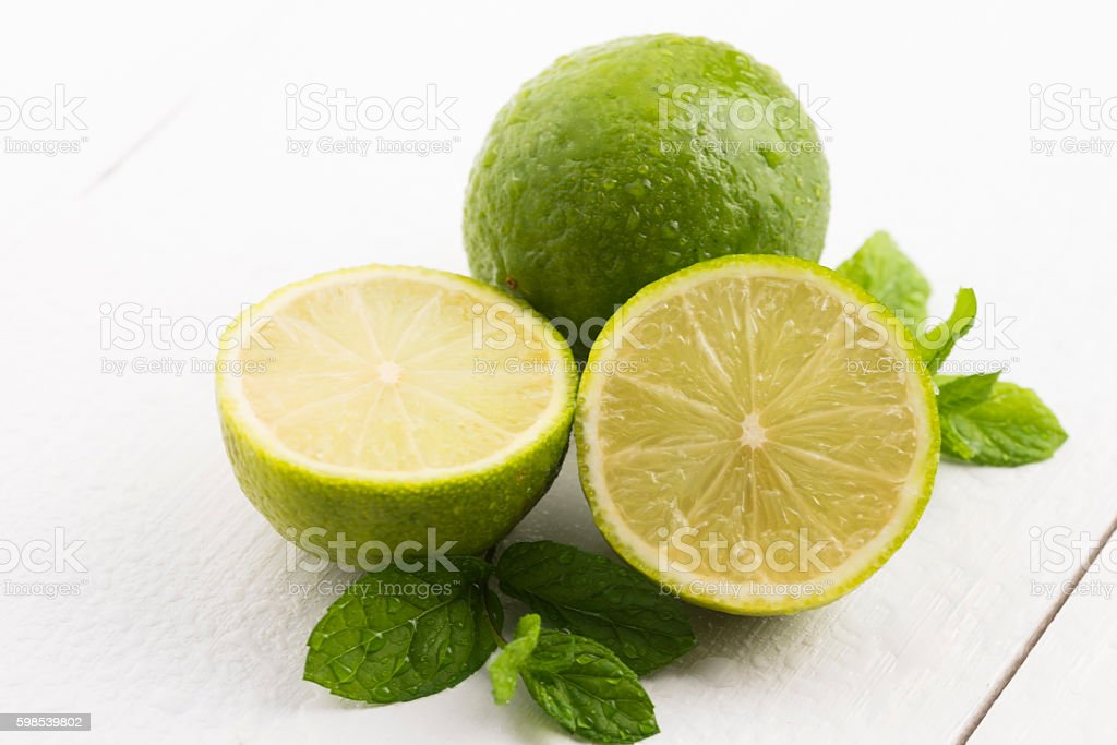 Green limes with mint and water drops on white background photo libre de droits