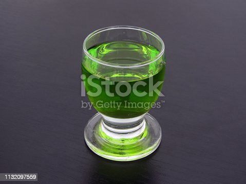 Close up shot of green liqueur in a glass, on black background