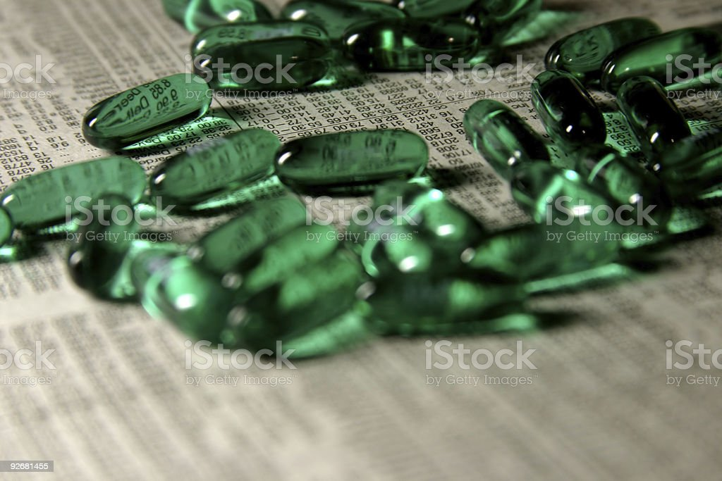 Green Liquid-Gel Pills on top of Newspaper Stock Quotes royalty-free stock photo