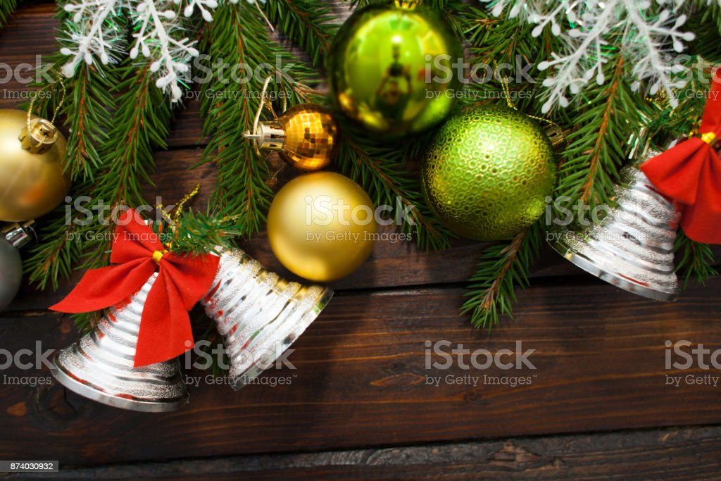 Green living spruce branches on a dark wooden background. New Year background with beautiful balls and white snow and bells. Top view stock photo