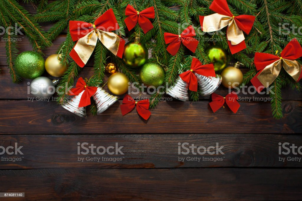 Green living spruce branches on a dark wooden background. New Year background with beautiful balls and red bows and bells. Top view stock photo