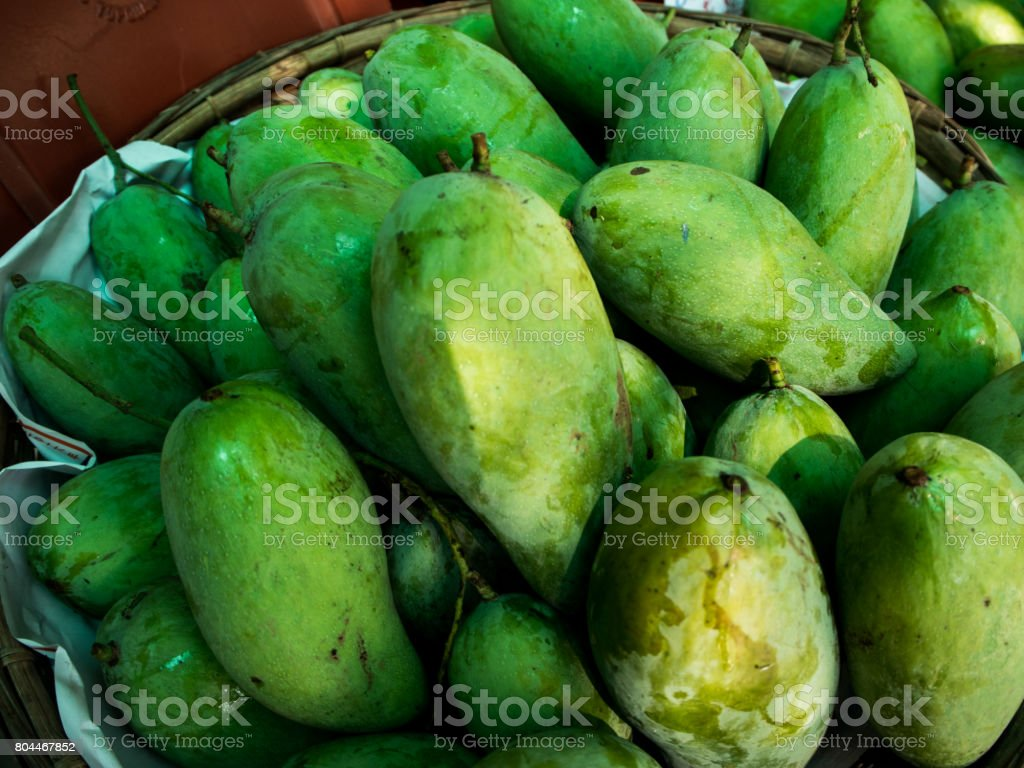 green mango for sale in a market. stock photo