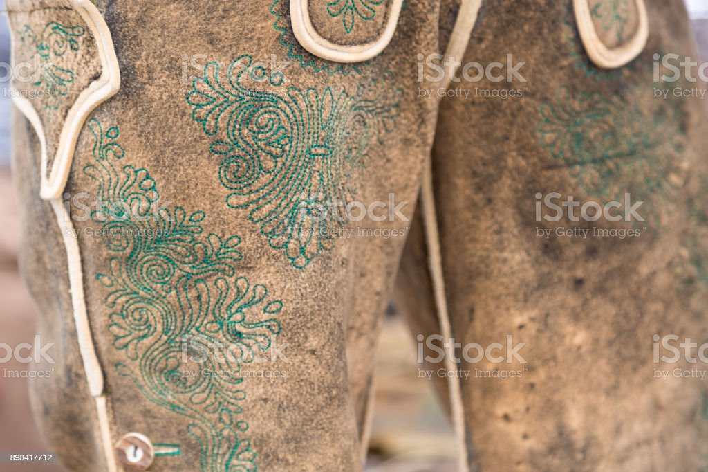 Green manual embroidery on deerskin leather trousers stock photo
