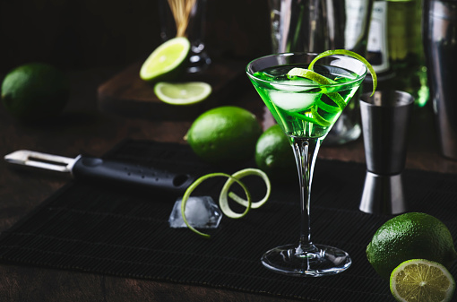 Green martini alcoholic cocktail in glass with dry gin, vermouth, liquor, lime zest and ice, steel bar tools, dark background