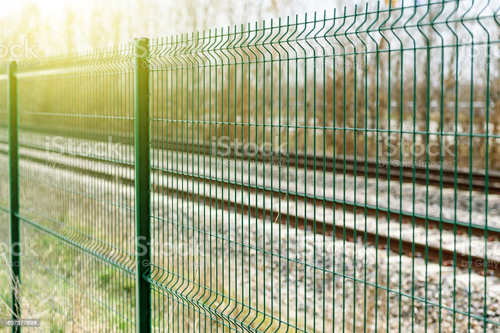 Green matallic fence in rural environment stock photo