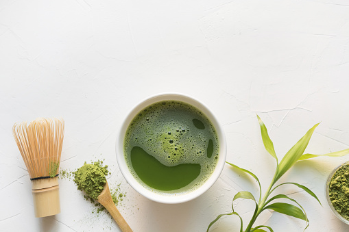Green matcha tea and bamboo whisk on white concrete table. Top view.