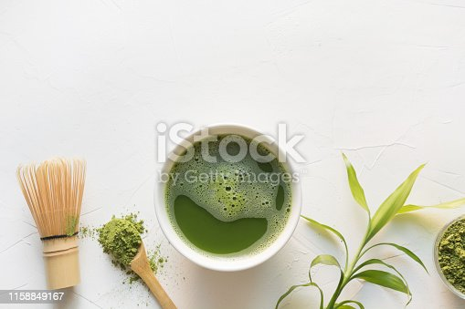 Traditional green matcha tea in bowl and bamboo whisk on white concrete table. Top view. Space for text.