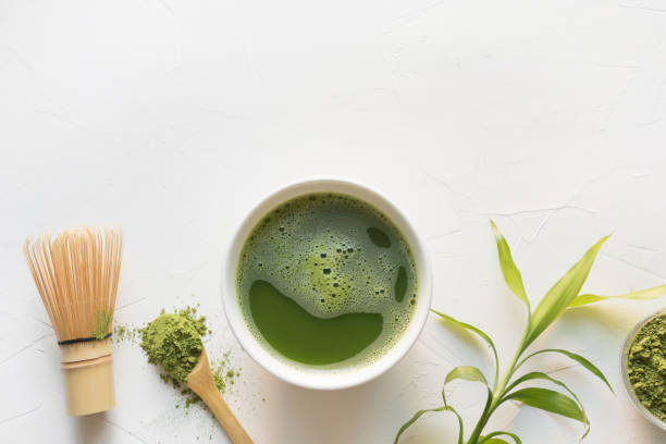 Green matcha tea and bamboo whisk on white concrete table. Top view. Traditional green matcha tea in bowl and bamboo whisk on white concrete table. Top view. Space for text. greentea stock pictures, royalty-free photos & images
