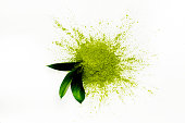 Green matcha tea powder and leaves on white background. Copy space