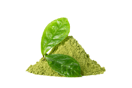 Green matcha tea powder with green wet leaves isolated on white