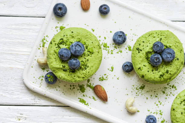 grünen matcha vegane rohe kuchen mit blaubeeren, minze und nüsse. gesund essen - grüntee kuchen stock-fotos und bilder