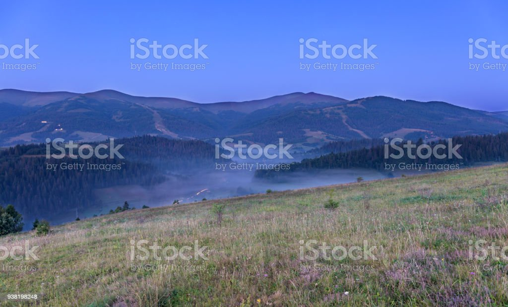 A green meadow and a gray curly fog on a hill in the background of the Carpathian Mountains in the early morning stock photo