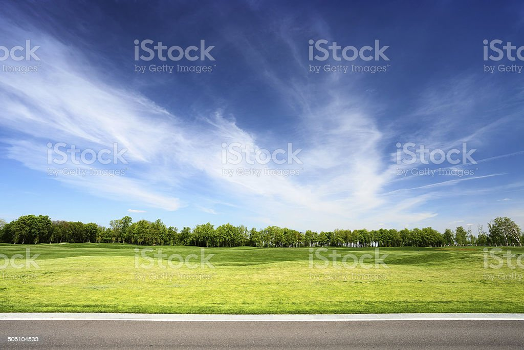 Green meadow and blue sky with asphalt road stock photo
