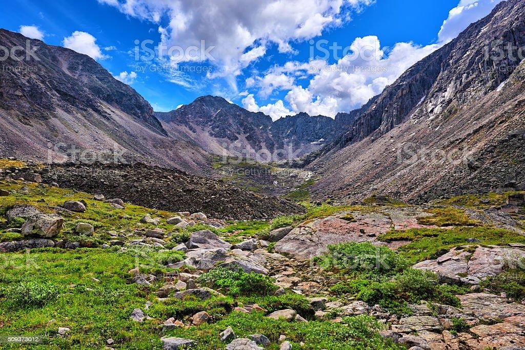Green meadow in mountain range . Sayan mountains stock photo