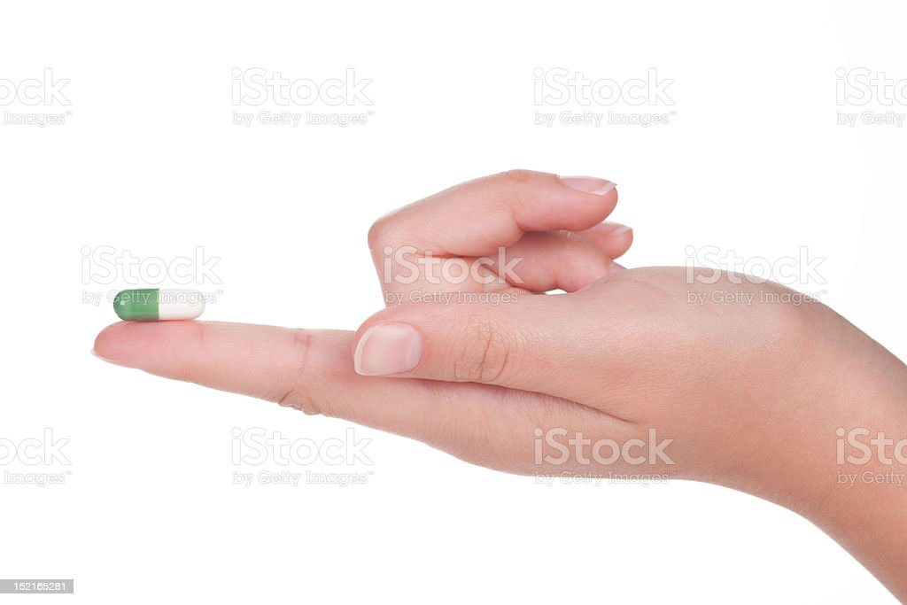 green medical capsule in a female hand, isolated royalty-free stock photo