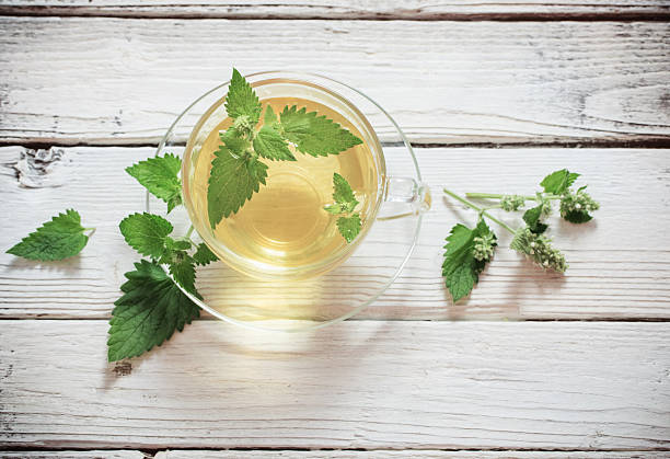 green melissa herbal tea in glass cup on wooden background stock photo