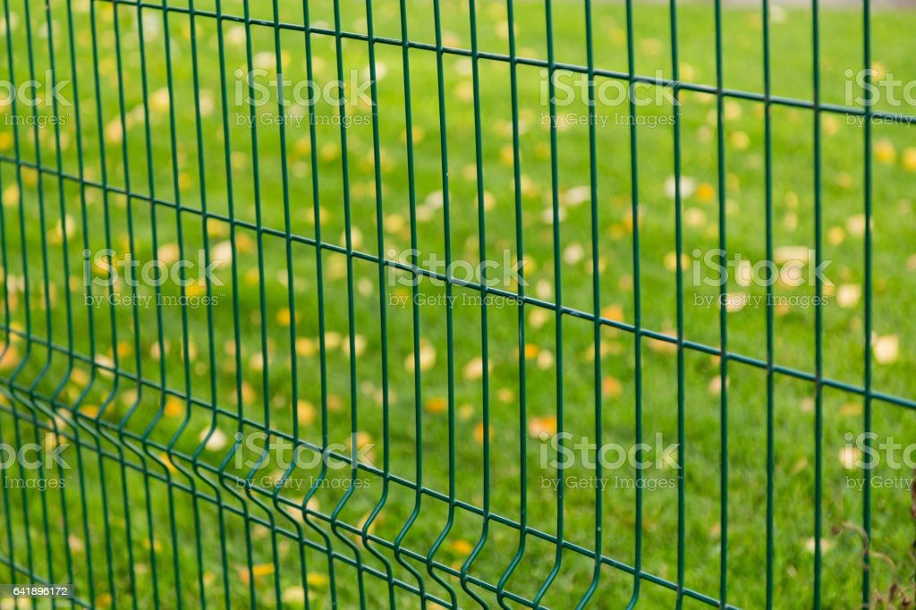 Green metal fence on blurred background stock photo