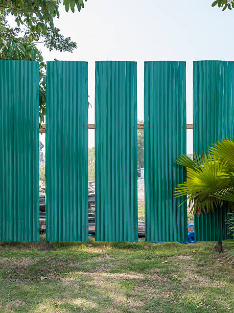 green metal fence - palisade boundary stock photos and pictures