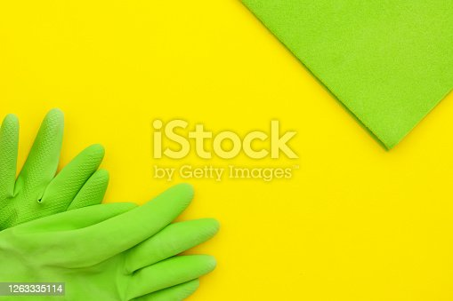 istock Green microfiber and green kitchen gloves on a light yellow background, top view. 1263335114