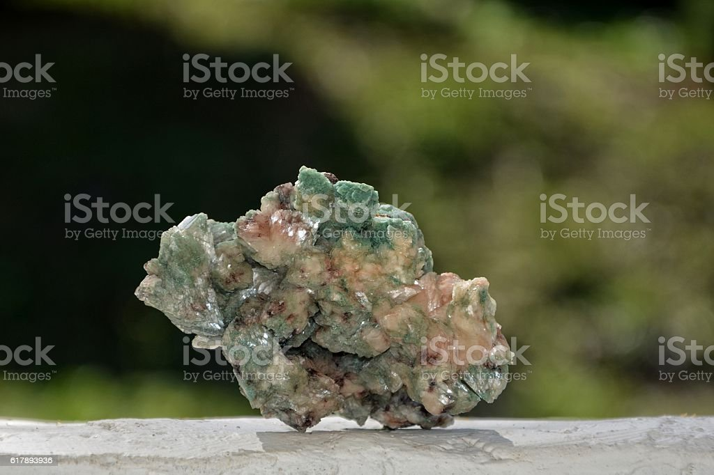 green mineral stone on white wall stock photo