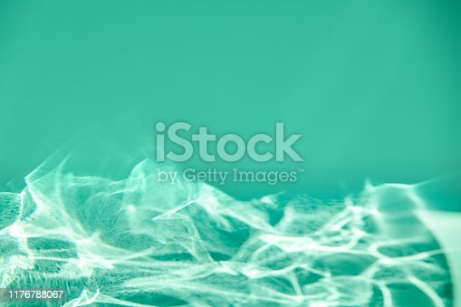 Green mint colored abstract background with light and shadows caustic effect. Light passes through a glass on textured paper. Trendy abstract simple design concept. Blank product display mockup.
