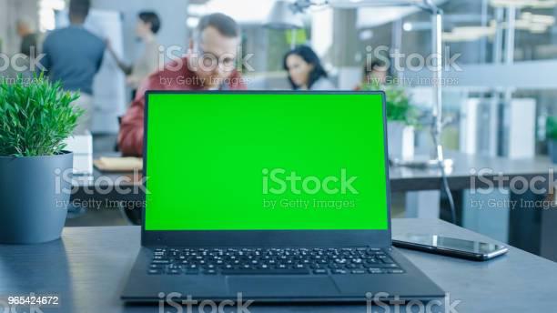Foto de Laptop De Tela Verde Mockup Em Cima Da Mesa Nos Fundo Jovens Profissionais Criativos Trabalhando No Escritório Moderno e mais fotos de stock de Adulto
