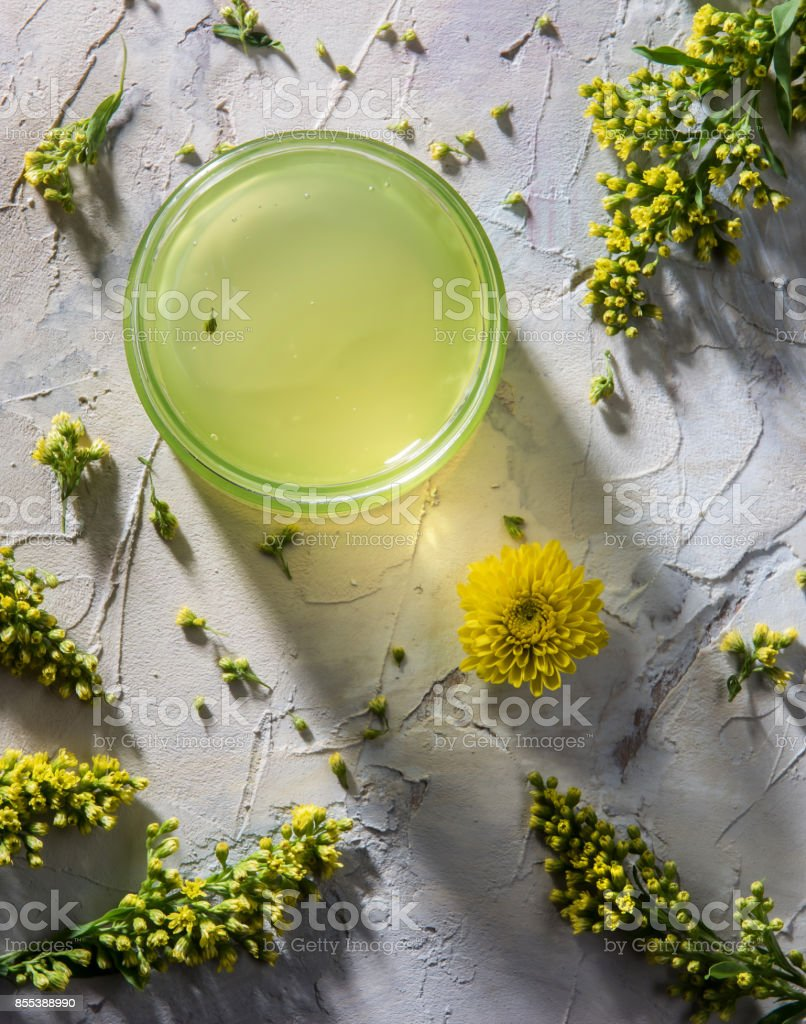 Green moisturizing cosmetic mask on the painted wooden background with yellow flowers around stock photo