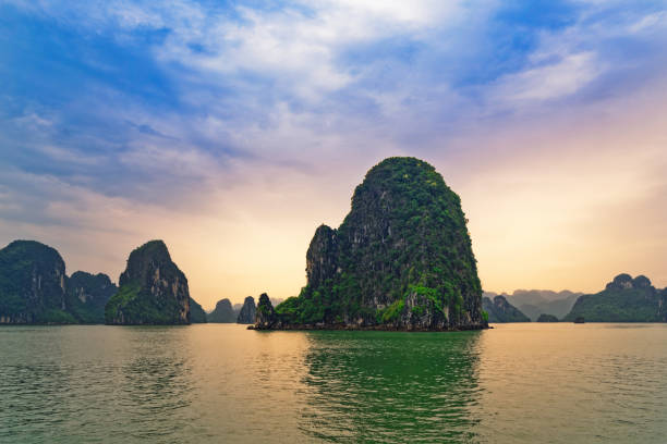 Green mountain island in Halong bay at sunset, Vietnam stock photo