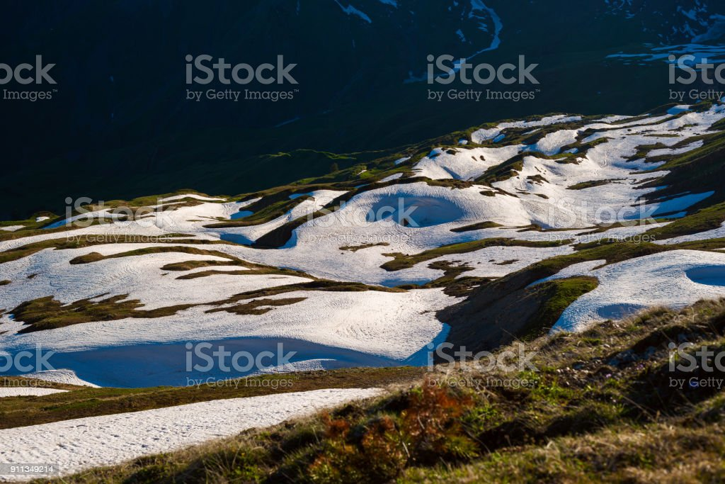 Green mountain slopes covered with remains of snow stock photo