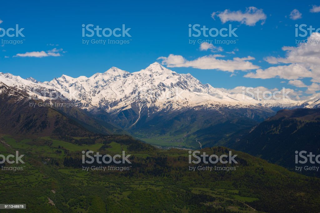 Green mountain valley against the background of snow-capped peaks stock photo