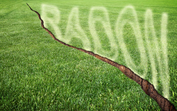 A green mowed lawn with a diagonal crack with radon gas escaping - concept image with copy space stock photo