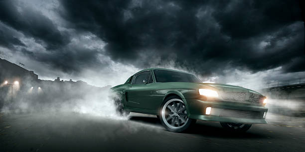 Green Muscle Car Burnout Green muscle car doing a burnout moving at speed at night on urban industrial road under dramatic stormy sky. Intentional heat haze from engine. sports car stock pictures, royalty-free photos & images
