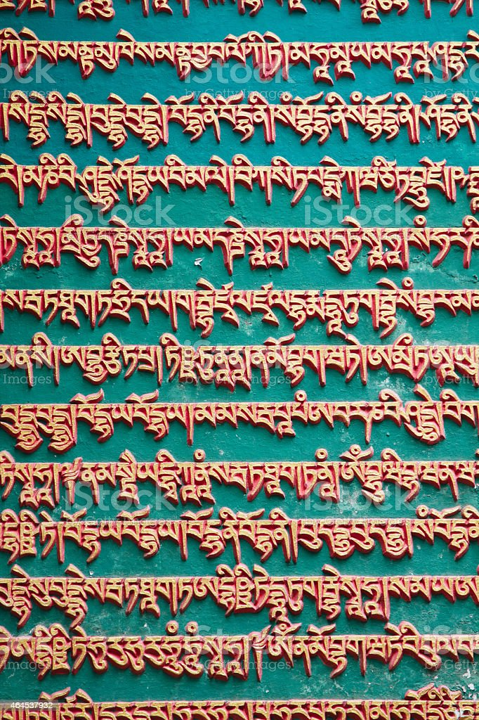 Green nepalese wall with gold mantras stock photo