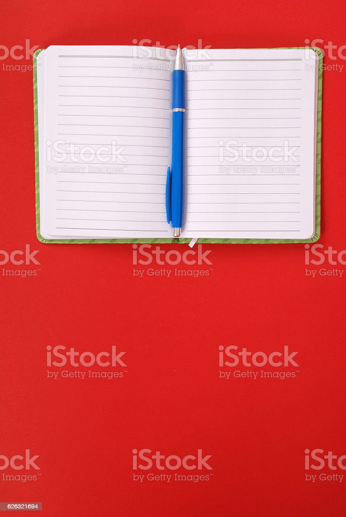 Green notebook and blue pen stock photo