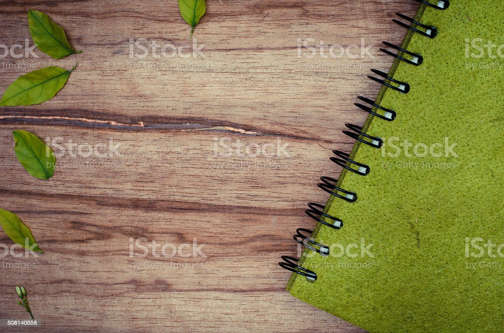 Green notebook on wood board stock photo