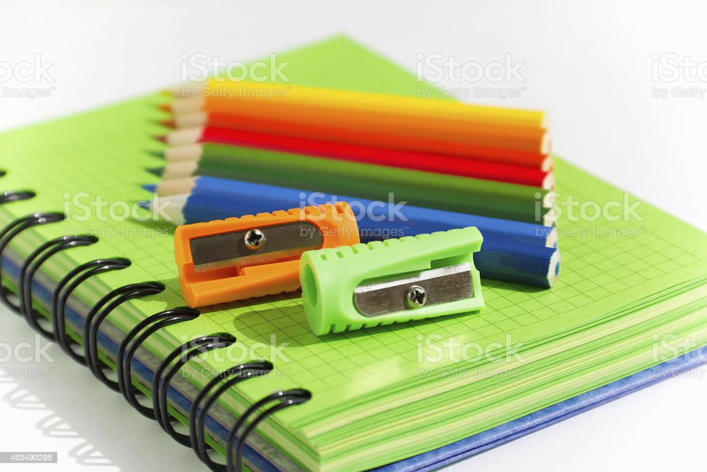 green notebooks with colored pencils and sharpeners royalty-free stock photo