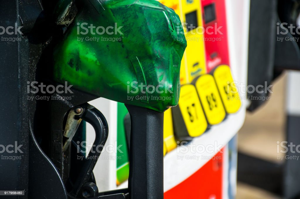 Green nozzle covered in corrosion and grime from carbon build up at the gas pump stock photo