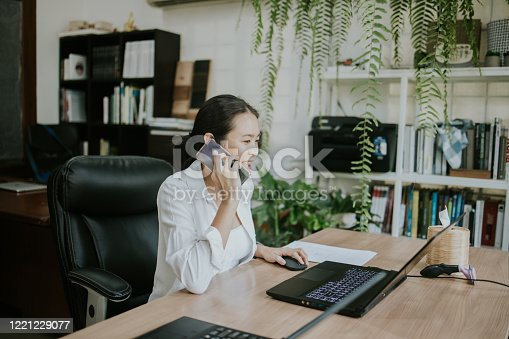 Thai architect woman using phone with her customer while working on computer laptop at the greenery office in the morning