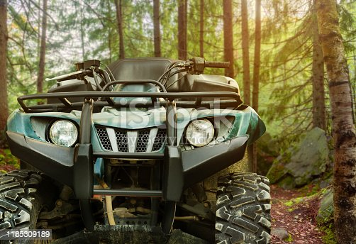 Photo of a green offroad hunting atv vehicle standing in forest, front view.