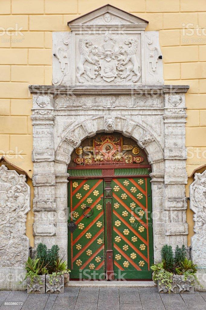 Green old fashioned wooden door on stone facade. Tallinn stock photo