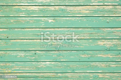 Green old weatherd wooden panels with textured green paint on the side of a shed in the countryside