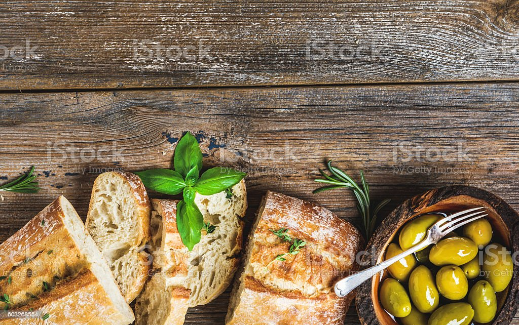 Green olives and slices of ciabatta over rustic wooden background stock photo
